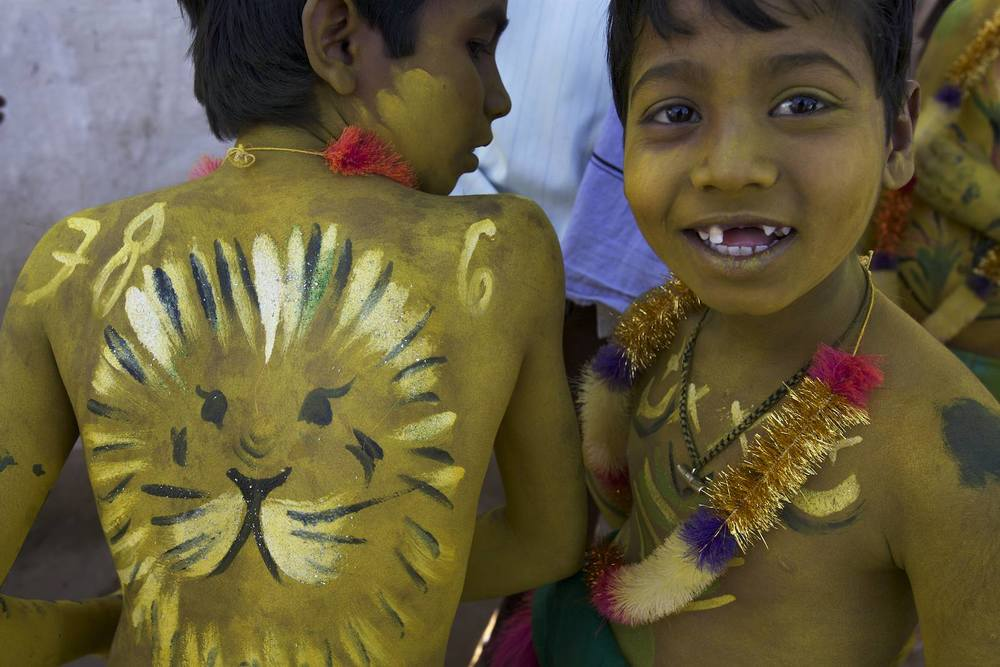 """Two boys with tiger motifs painted on their bodies in celebration of Muharram, the Muslim new year in Umaria, India. In some parts of the Muslim work, people paint their bodies and wear mask to impersonate tiges and dance """"Pulikali"""" or """"the tiger dance""""."""